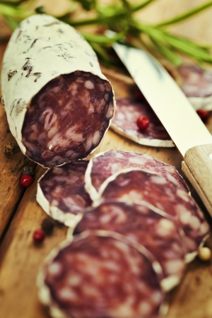 air dried salami: Close-up traditional sliced meat sausage salami on wooden board with rosemary