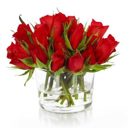 白で隔離される花瓶に美しい赤いバラ