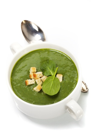 Traditional Spinach cream soup with croutons and fresh spinach leaf on top photo