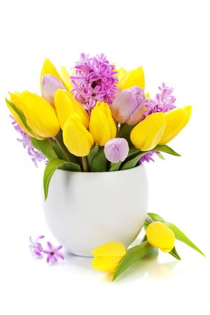 Beautiful spring flowers in vase over white photo