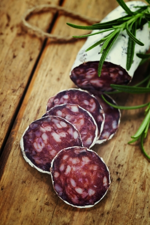 air dried salami: Close-up traditional sliced meat sausage salami on wooden board with  rosemary Stock Photo