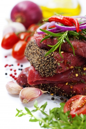 Raw beef steak and vegetables over white photo