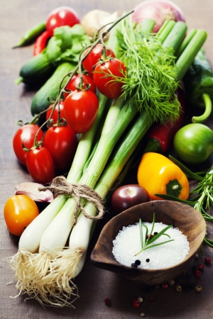 healthy living: fresh spring onions and vegetables on a wooden board