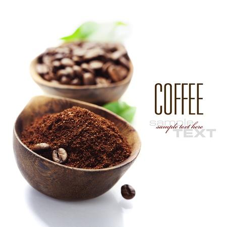 bönor: Trä Skålar med kaffebönor och malet kaffe över vita (med exempeltext)