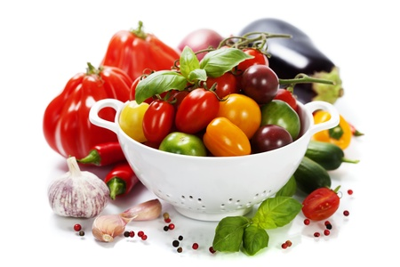 colander: Assorted colorful tomatoes and vegetables in colander on white background - healthy eating concept