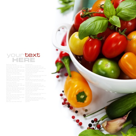 Assorted colorful tomatoes and vegetables in colander on white background - healthy eating concept (with easy removable sample text)