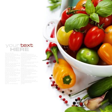 Diverse kleurrijke tomaten en groenten in vergiet op witte achtergrond - gezond eten concept (met gemakkelijk verwijderbare voorbeeld tekst)