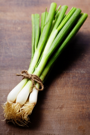 spring onions: fresh spring onions on a wooden board