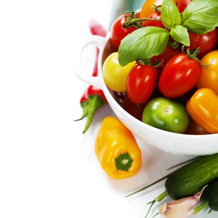 a colander: Assorted colorful tomatoes and vegetables in colander on white background - healthy eating concept