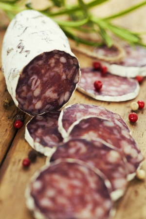 longaniza: Close-up traditional sliced meat sausage salami on wooden board withrosemary