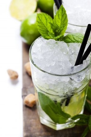 Mojito cocktail with ingredients on wooden background