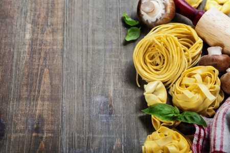 rollingpin: Fresh pasta and italian ingredients on wooden table Stock Photo