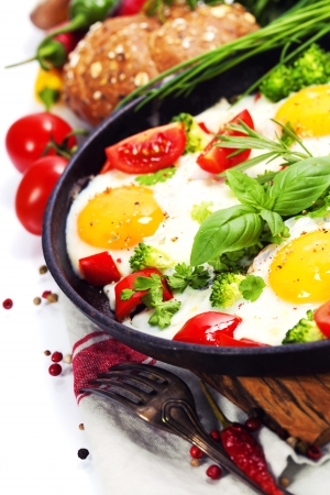 rustic food: Fried eggs with fresh vegetables over white (health, breakfast or vegetarian concept)