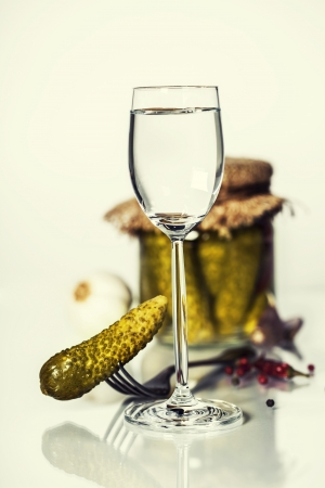 Russian vodka with pickled cucumbers on white  photo