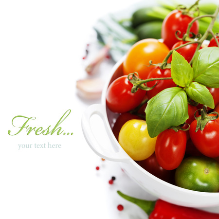 a colander: Assorted colorful tomatoes and vegetables in colander on white background - healthy eating concept (with easy removable sample text)