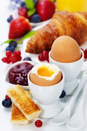 Delicious breakfast with eggs, fresh croissants, fructs and juice