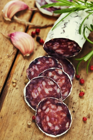 longaniza: Close-up traditional sliced meat sausage salami on wooden board with head of garlic and green herbs  Stock Photo