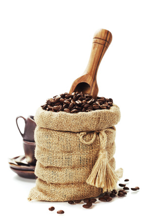 coffee sack: Coffee beans in burlap sack with wooden scoop  over white