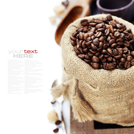Koffiebonen in jutezak met houten lepel over wit (met voorbeeld tekst)