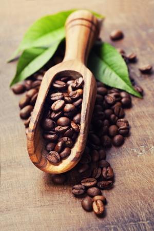 semilla de cafe: Los granos de café y una vieja cuchara de madera Foto de archivo