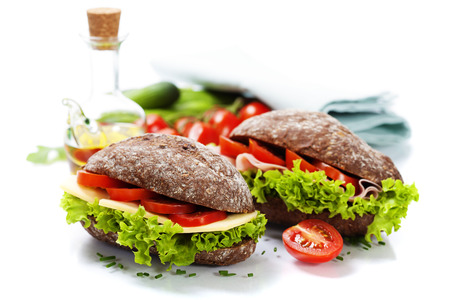 Grain bread sandwiches with ham,cheese and fresh vegetables over white - healthy eating concept photo