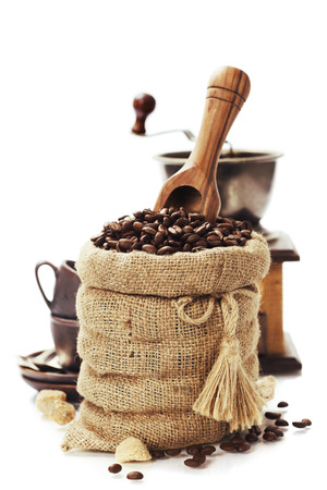 Coffee beans in burlap sack with wooden scoop  over white photo