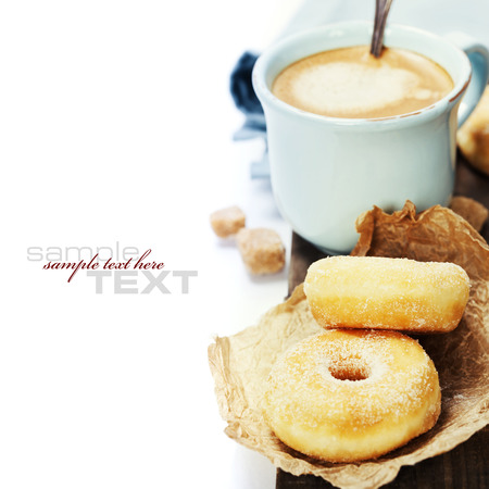 Coffee break with fresh sugary donuts over white background (with easy removable sample text) photo