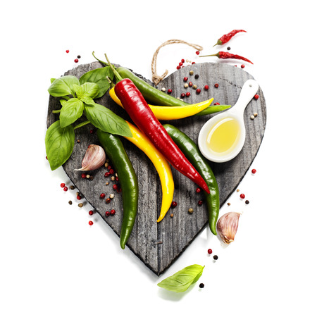 Fresh vegetables on heart shaped cutting board over white (health or vehetarian concept) photo