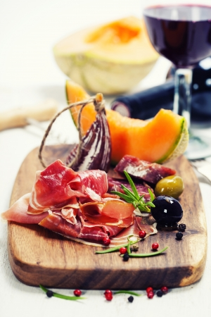 jamones: Cocina italiana. Antipasto. Prosciutto, melón, salami, aceitunas y vino