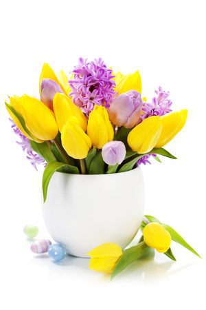Easter composition with Beautiful spring flowers in vase over white photo