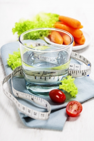 Fresh vegetables and measurement tape - diet and healthy eating concept - over white Stock Photo