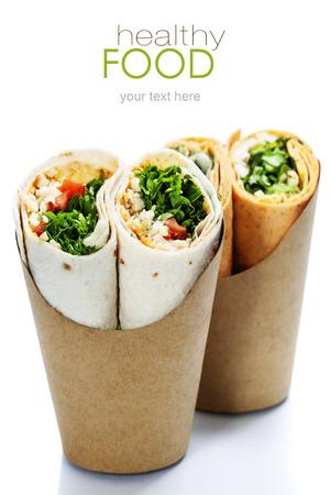 sandwich: Abrigos de la tortilla con pollo y verduras frescas aisladas en blanco