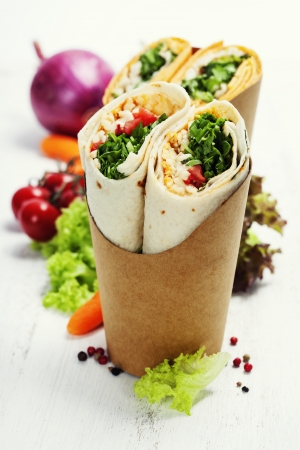 take away: tortilla wraps with chicken and fresh vegetables isolated on white Stock Photo