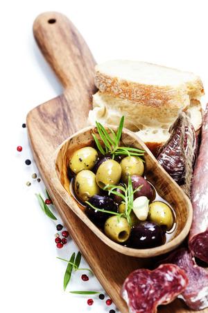 salami: Salami italiano con aceitunas y pan ciabatta sobre fondo blanco