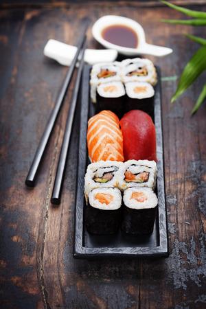 木製の背景に箸で寿司