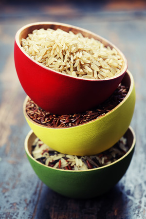 wild rice: Three bowls with different types of rice on wooden background