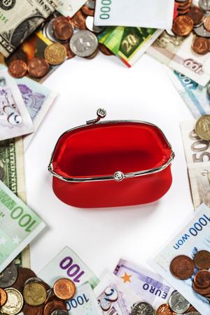 Monedas y billetes extranjeros marco con bolso rojo. photo