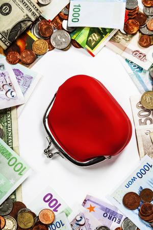 Monedas y billetes extranjeros frame con el monedero rojo. photo