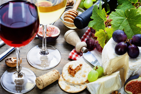 Wine, grape and cheese on wooden  photo