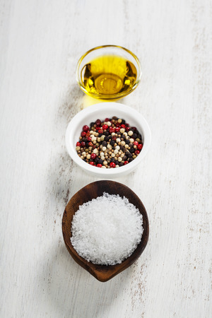 salt pepper: Salt, pepper and olive oil on a wooden board Stock Photo