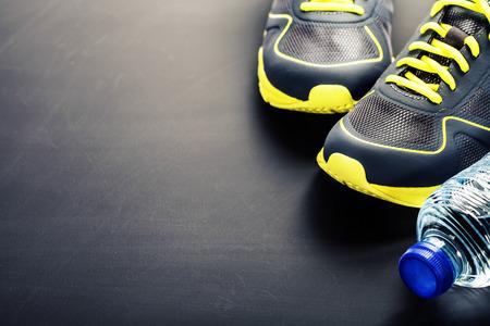pista de atletismo: Zapatos del deporte y el agua en el fondo se