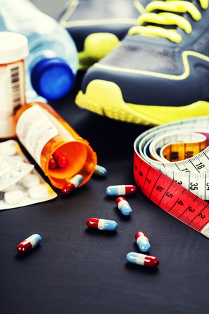 Different tools for sport and pills (Vitamins or Fitness Supplement) on grey background - sport, health and diet concept photo