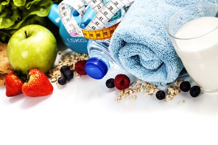 Different tools for sport and healthy food for diet on white background - sport, health and diet concept Stock Photo
