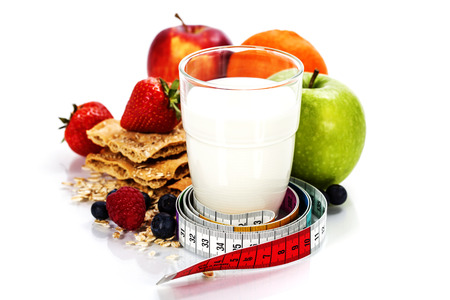 Glass of milk or  kefir, fruits, crispbreads, berries and measuring tape isolated on white  photo