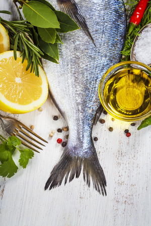 sea bass: fresh dorado fish and vegetables on wooden board - food and drink