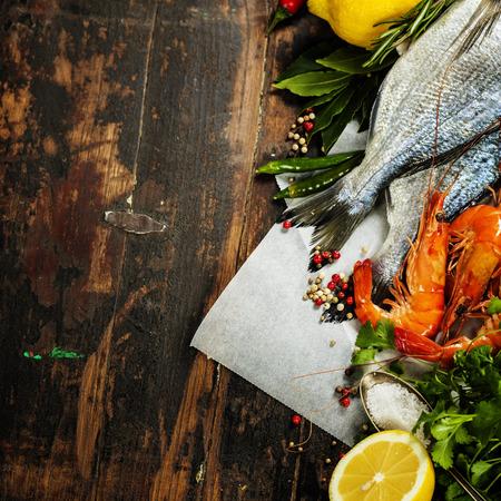 �shrimp: Pescados frescos del dorado y camarones en la tabla de madera con ingredientes de comida y bebida