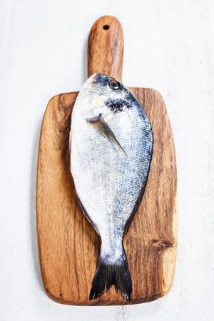 Delicious fresh dorado fish on wooden kitchen board photo