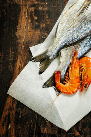 fresh dorado fish and shrimps on wooden board - food and drink photo
