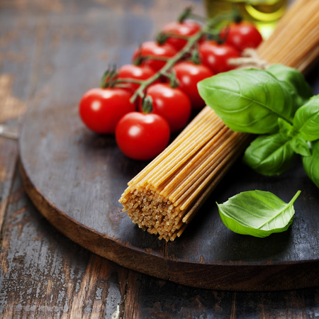 carte: Spaghetti and tomatoes with herbs on an old and vintage wooden table