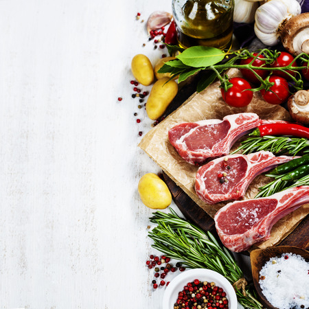 Raw lamb cutlets with vegetables, herbs and spices photo